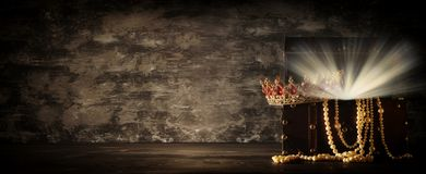 Image of mysterious opened old wooden treasure chest with light and queen/king crown with red Rubies stones. fantasy medieval peri. Od. Selective focus royalty free stock photos