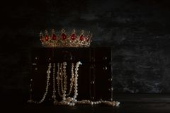 Image of mysterious opened old wooden treasure chest with light and queen/king crown with red Rubies stones. fantasy medieval peri. Od. Selective focus stock image