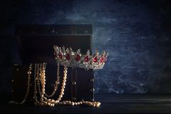 Image of mysterious opened old wooden treasure chest with light and queen/king crown with red Rubies stones. fantasy medieval peri. Od. Selective focus stock photos