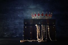 Image of mysterious opened old wooden treasure chest and queen/king crown with red Rubies stones. fantasy medieval period. Selecti. Ve focus stock image