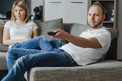 Image naturelle, de mode de vie des couples attrayants se reposant sur le divan et préparant pour observer un film Photographie stock libre de droits