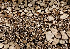 Wood Stack of Various Sizes with Rounds. An image of the neat stacking of large and small fire wood split and rounds piled out of the weather for a cold winter royalty free stock photo