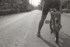 Image noire et blanche abstraite de femme se reposant sur la vieille bicyclette et montant sur la route bétonnée pendant le matin images stock