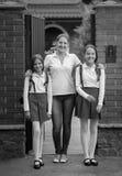 Image noire et blanche de famille heureuse posant devant la grande maison avant de laisser à l'école Photo stock