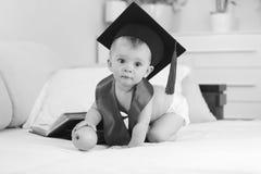 Image noire et blanche de garçon de génie dans le chapeau d'obtention du diplôme se reposant sur le lit avec la pomme et regardan Images libres de droits