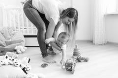Image noire et blanche de jeune mère essayant de calmer vers le bas son bébé garçon pleurant image stock