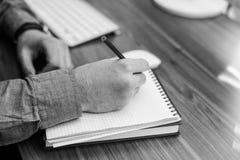 Image noire et blanche de l'écriture de main dans le carnet sur la table en bois Photos libres de droits