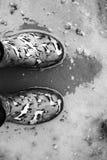 Image noire et blanche des bottes de pluie dans un magma images stock