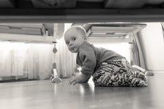 Image noire et blanche du garçon de sourire d'enfant en bas âge s'asseyant sur le plancher en bois à la chambre à coucher et rega Photos libres de droits
