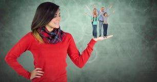 Image numérique de belle femme avec la famille en main se tenant sur le fond vert Images stock