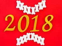 Auspicious new year 2018. An image of number 2018 in gold with white bone shape dog treats on bright red paper background, symbolizing auspicious year 2018, Year stock images