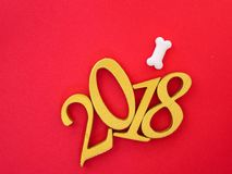 Auspicious year 2018. An image of number 2018 in gold with white bone shape dog treats on bright red paper background, symbolizing auspicious year 2018, Year of Stock Photos