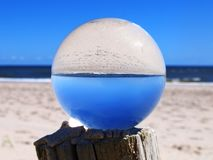 Ocean Image Inverted in Lens Ball. The image of the ocean is inverted in a lens ball resting on top of a wooden post royalty free stock photo