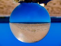 Ocean Image Inverted in Lens Ball. The image of the ocean is inverted in a lens ball resting on top of a wooden post royalty free stock photography