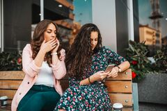 Free Image Of Curious Woman Spying And Peeping At Smartphone Of Her Friend, While Talking On Mobile Phone Stock Photo - 181643560