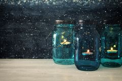 Free Image Of Vintage Decorative Magical Mason Jars With Candle Light On Wooden Table. Glitter Overlay Royalty Free Stock Photos - 100061258