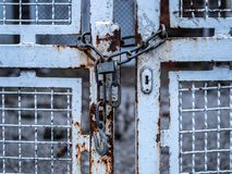 Image of old chain with padlock and white iron gate stock images