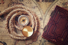 Image of old compass and rope next to old book on vintage map Royalty Free Stock Photo