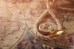 Image of old compass and rope on vintage map Stock Photos