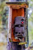 Image of an old dirty control box with cobwebs on a wooden pole stock photography