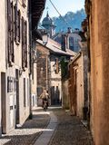 Image of old man from behind cycling through narrow street in an Italian old town stock images