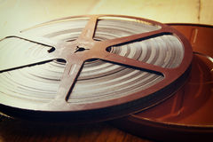 Image of old 8 mm movie reel over wooden background. retro style image Royalty Free Stock Photo