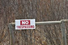 Old No Trespassing Signage. An image of an old red and white no trespassing sign posted to a wooden fence post Royalty Free Stock Photography