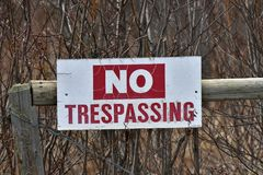 Old No Trespassing Signage. An image of an old red and white no trespassing sign posted to a wooden fence post Royalty Free Stock Image