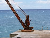 Image of old rusty habour crane on a pier stock images