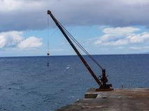 Image of old rusty habour crane on a pier stock photography