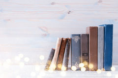 Image of old vintage books on a wooden shelf. Glitter overlay Royalty Free Stock Photography
