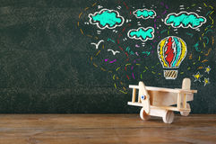 Image of old wooden airplane toy on wooden table in front of set of info graphics over textured chalkboard Stock Photography