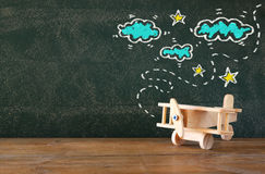 Image of old wooden airplane toy on wooden table in front of set of info graphics over textured chalkboard Stock Photos