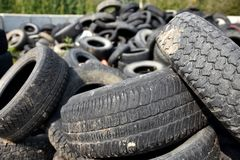 Old Damaged and Worn Out Tires for Recycling. An image of old worn out tires in a landfill waiting to be collected and recycled stock photos