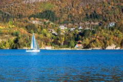 A Lone White Sailboat in Autumn stock photography