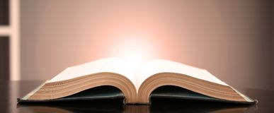 Image of an open book with a beautiful yellow light on a black background stock photo