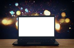 open laptop with white screen on wooden table in front of abstract glitter background Stock Photos