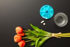 Open pillbox with some pills glass of water and tulips. An image of an open pillbox with some pills glass of water and tulips stock photos