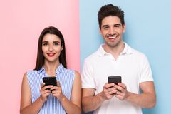 Image of optimistic couple using cell phones together, isolated. Image of optimistic couple using cell phones together isolated over colorful background stock image