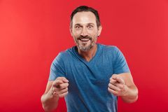 Image of optimistic man 30s in casual t-shirt smiling and pointi. Ng fingers on camera isolated over red background Royalty Free Stock Photo