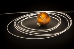 An orange christmas ball with light streaks stock images