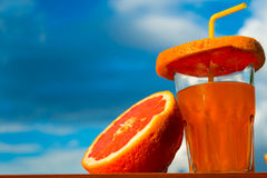 Image of orange juice. And orange against the sky close-up Stock Images