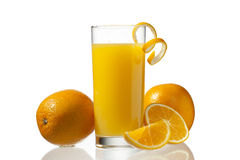 Image of orange slice with orange in glass. View of glass of orange juice with straw while orange fruits and some slices on white surface Royalty Free Stock Image