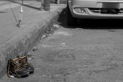Image of a pair of old shoes abandoned in the street next to a sidewalk stock photos