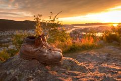 A Pair of Worn Hiking Boots at Sunset. Image of a pair of worn hiking boots on mountain, view towards the sun and city center at cloudy orange sunset royalty free stock images