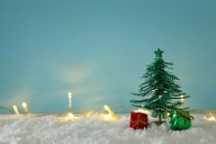 Image of paper christmas trees over white snow and golden garland lights. stock photography