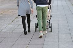 Parents with a child in a stroller walk along the street Royalty Free Stock Photo