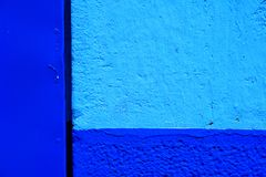 Vibrant blue and pale blue background. Image of part of a wall painted in two tones of blue stock image