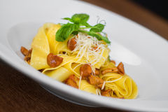 Image of pasta with chanterelle served in white dish. Close image of pasta with cheese Stock Photo