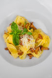 Image of pasta with chanterelle served in white dish. Close image of pasta with cheese Royalty Free Stock Image